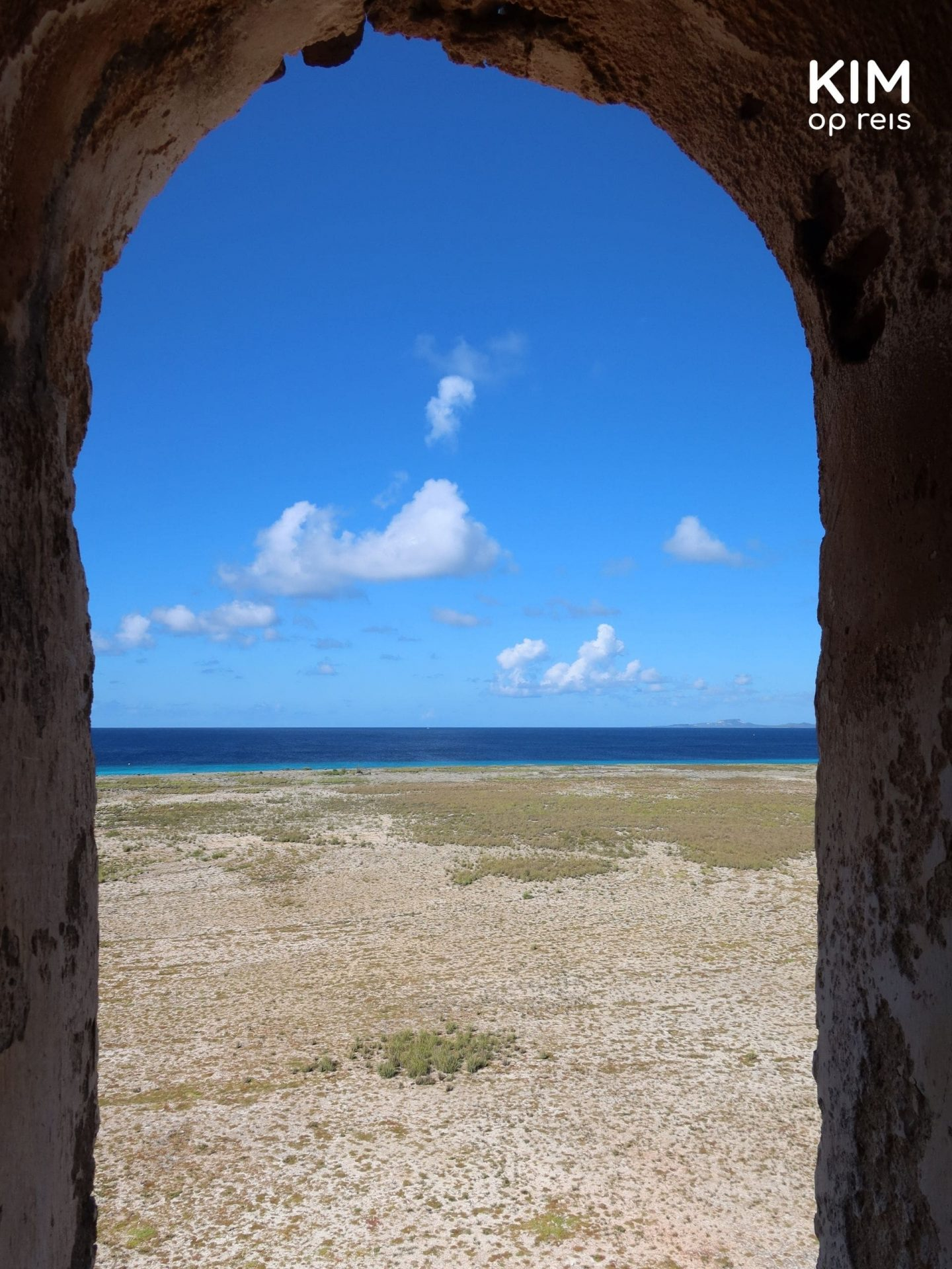 Day trip Klein Curaçao, viewpoint lighthouse: through a lighthouse window a view of a dry landscape with the sea in the distance
