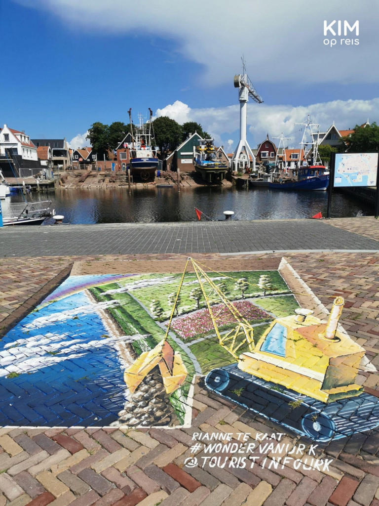 3D graffiti on Urk - on the ground a painting of a meadow with a bulldozer and in the background the harbor of Urk